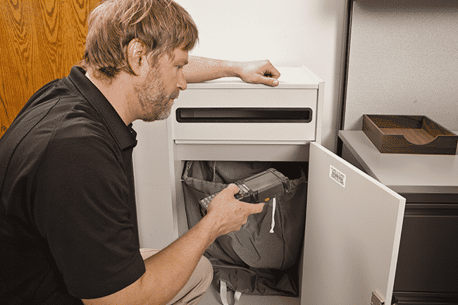 Employee performing scheduled pickup of sensitive documents from a shredding collection console