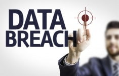 Business man pointing to transparent board with text: Data Breac