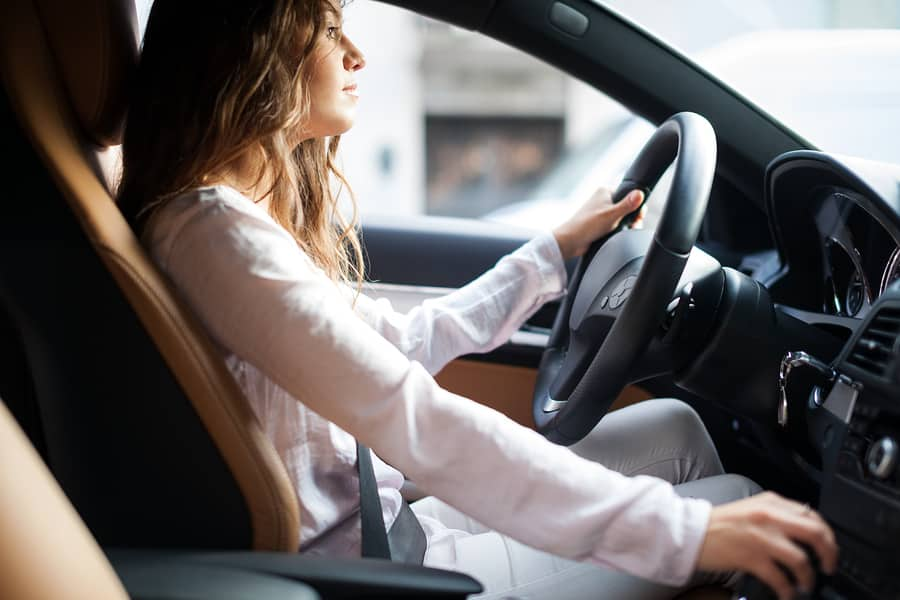 Young woman driving to drop off shredding