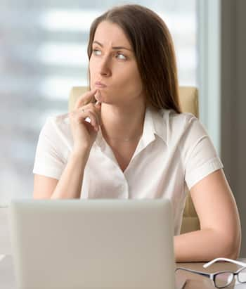 Woman with pensive facial expression looking aside while sitting at workplace. Unsure businesswoman thinking about difficult question. Female office worker doubted because of uncertain situation