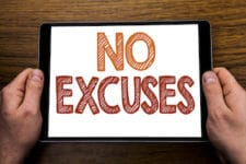 Hand writing text caption No Excuses. Business concept for Stop Ban for Excuse Written tablet laptop, wooden background with businessman hand, finger holding PC.