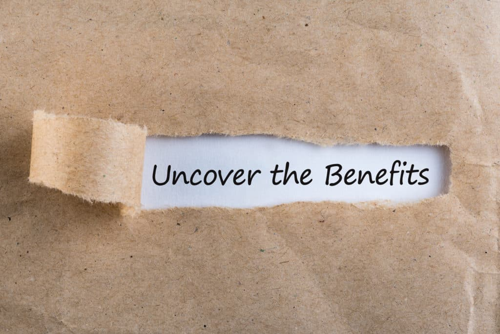 Uncover The Benefits text on brown envelope. Word Uncover The Benefits on torn paper. Concept Image..