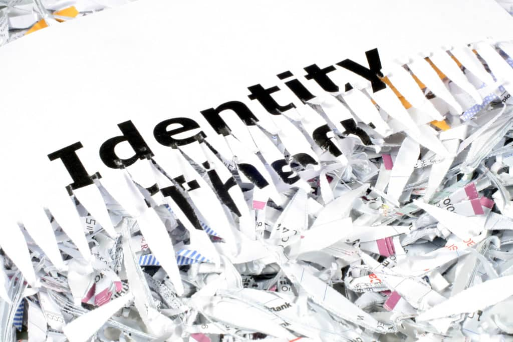 this is an image of the words identity theft shredded laying on shredded paper.