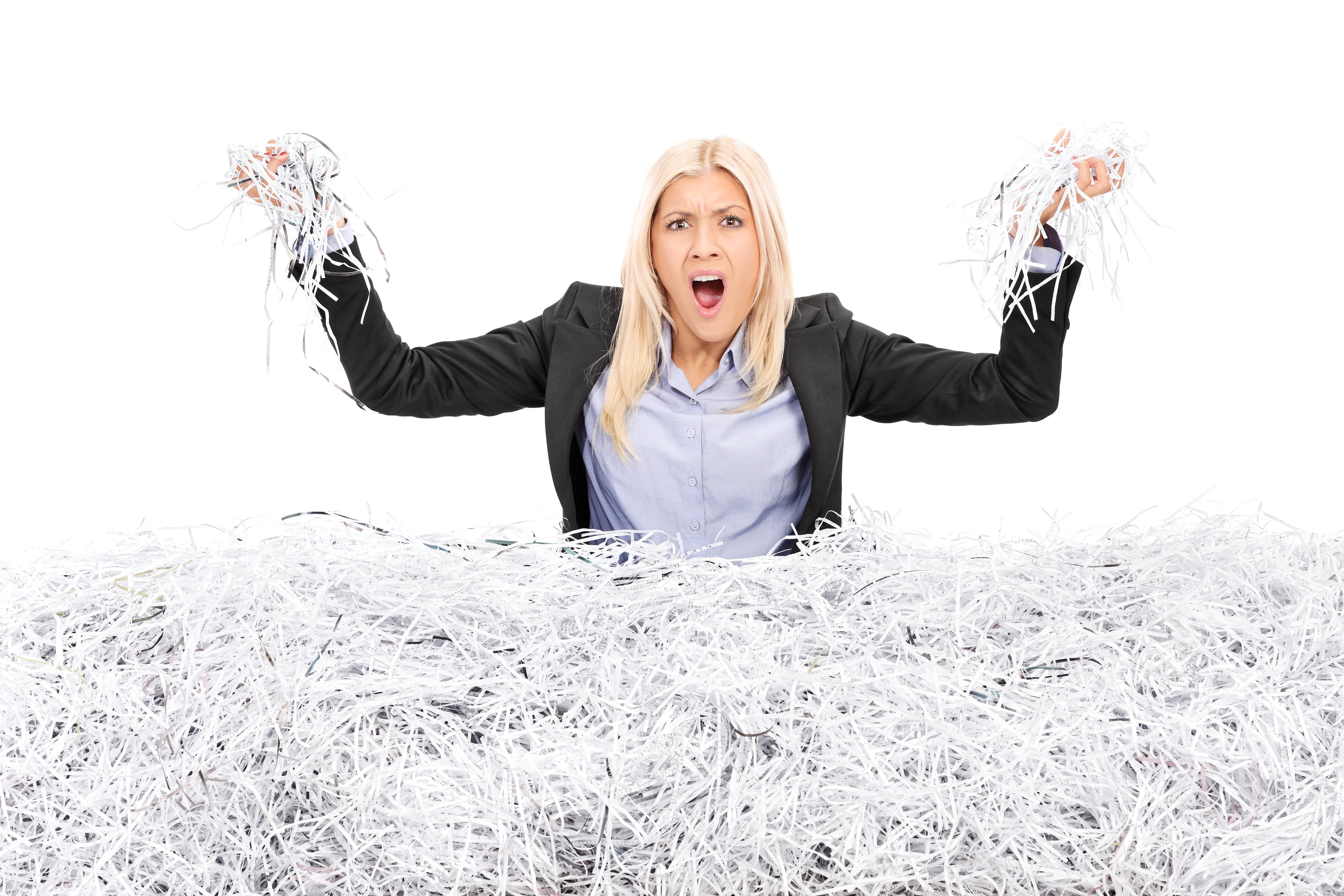 Angry businesswoman in a pile of shredded paper isolated on white background