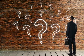 Businessman looking and thinking in front of a brick wall with the question marks icon . Business question concept
