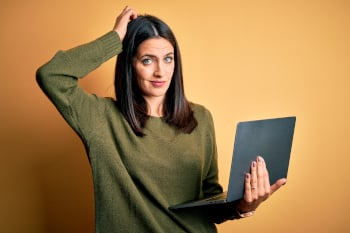 Young brunette woman with blue eyes working using computer laptop over yellow background confuse and wondering about question. Uncertain with doubt, thinking with hand on head. Pensive concept.