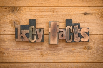 Key facts , phrase written with vintage letterpress printing blocks on rustic wood background.