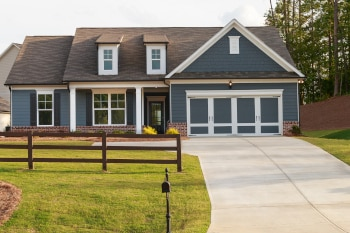 A gray ranch style model house in a new neighborhood.