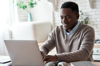 Smiling professional black business man using laptop computer working from home office. Happy african-american male customer makes ecommerce delivery order from supermarket typing on pc sits at kitchen table